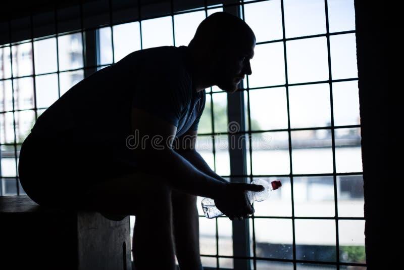 休息与一个瓶的开会在立方体的水运动员的剪影 在全景窗口前面 图库摄影