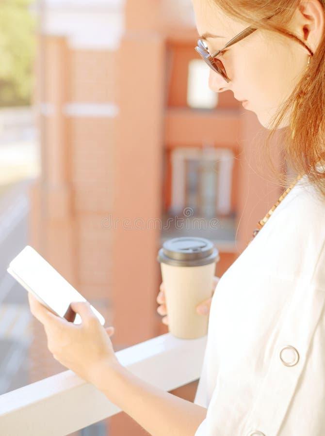 休息与咖啡的妇女和智能手机在阳台 图库摄影