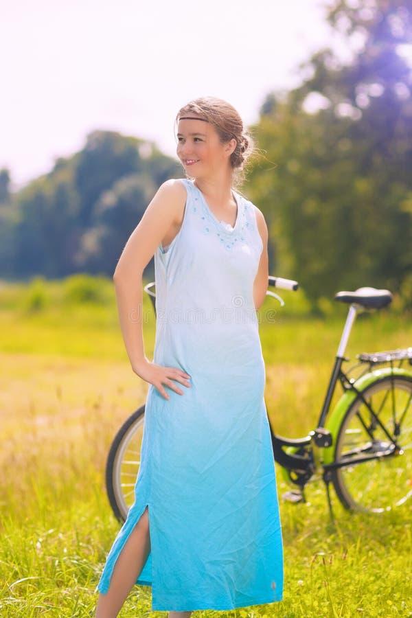 休息与她的自行车的美丽的年轻白种人妇女户外 免版税库存照片