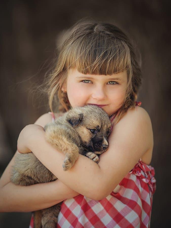 休息与狗的逗人喜爱的孩子 免版税图库摄影