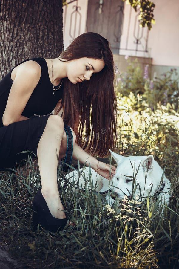 休息与白色爱斯基摩的女孩 免版税图库摄影