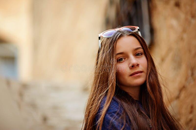 休息可爱的女孩和的眼镜画象便衣的户外享受天气,正面青少年的女性 免版税库存照片