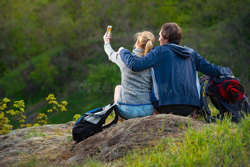 休息和享受美好的自然的年轻夫妇远足者观看a 免版税库存照片