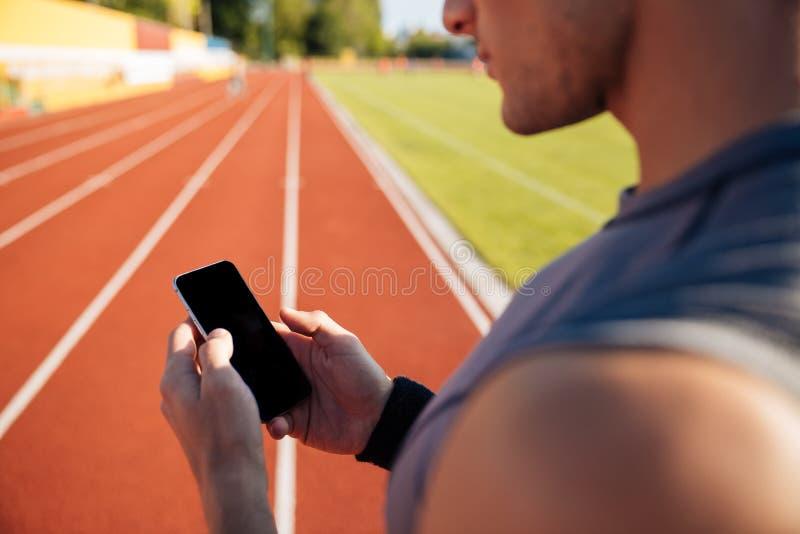 休息和使用智能手机的一个英俊的人的播种的图象 免版税库存照片