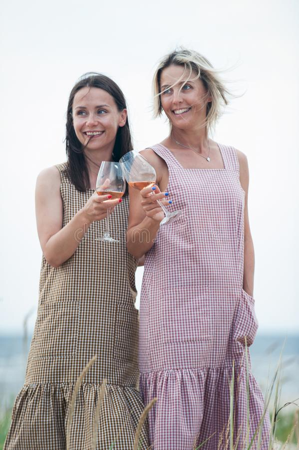 休息和喝白色夏天酒的两名年轻可爱的妇女 免版税库存照片