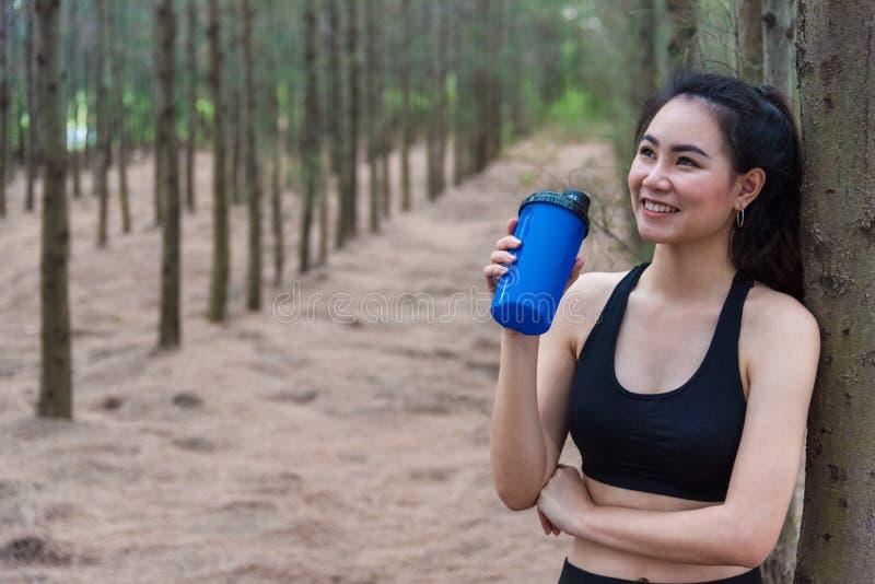 休息和拿着饮用水瓶和放松在森林中部的秀丽亚裔体育妇女在疲乏以后从跑步 库存图片