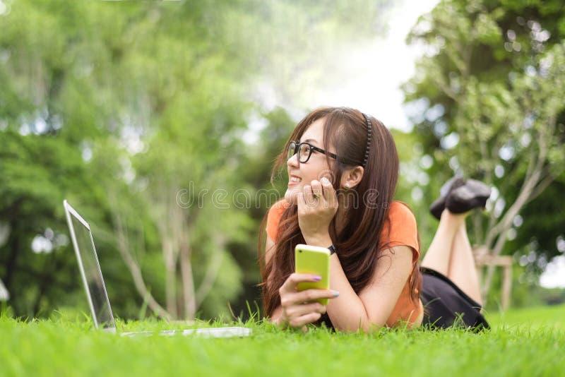 休息和看此外在有智能手机的公园的愉快的亚裔妇女 人们和生活方式概念 技术和秀丽题材 免版税库存图片
