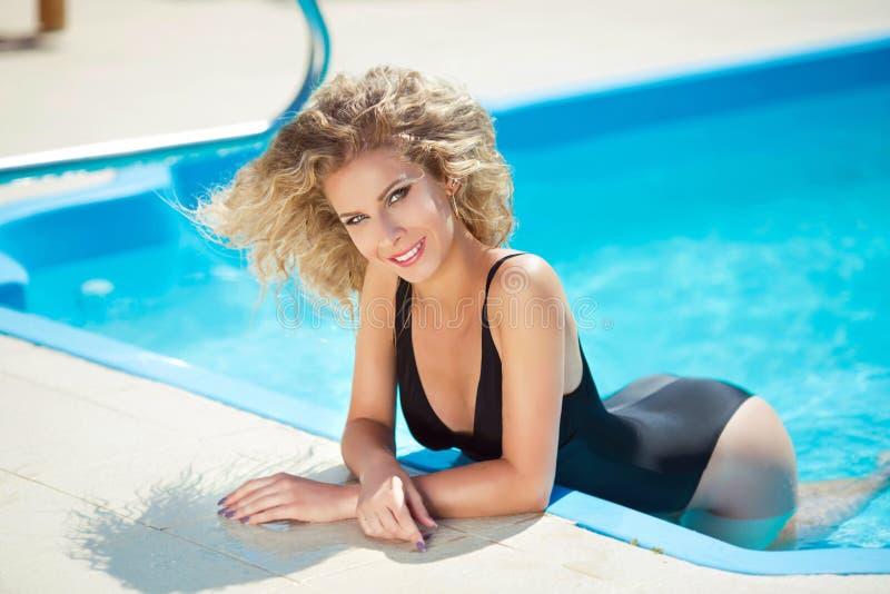 休息和被晒黑的比基尼泳装的美丽的微笑的肉欲的妇女  免版税库存照片