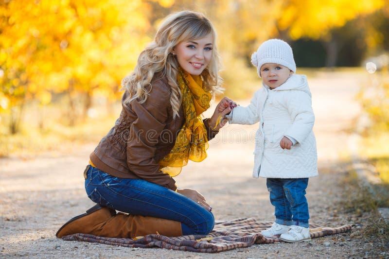 休息在一个公园的妈妈和女儿在秋天 免版税图库摄影