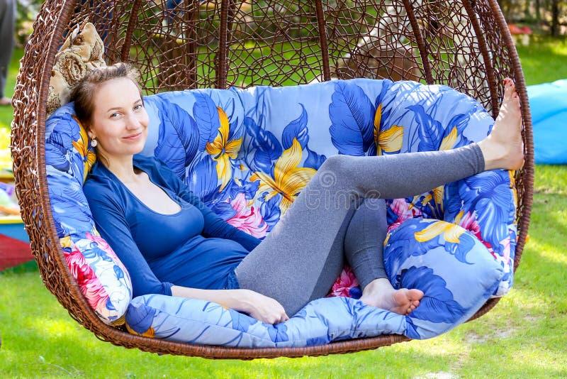 休息在一把暂停的棕色椅子的美丽的年轻孕妇户外 免版税图库摄影