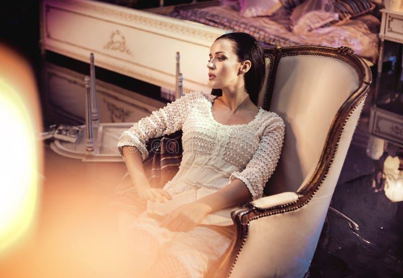 休息在一把豪华,古色古香的扶手椅子的Beautfiul少女 免版税库存图片