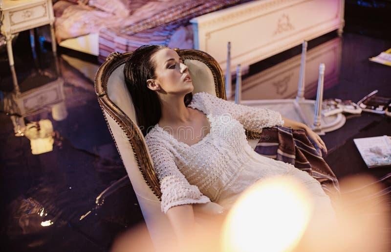 休息在一把豪华,古色古香的扶手椅子的Beautfiul少女 免版税库存照片