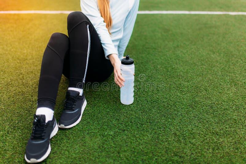 休息在一种好锻炼以后的女孩 在锻炼以后的女孩,在橄榄球场的饮用水 美丽的女孩画象体育的 免版税库存照片
