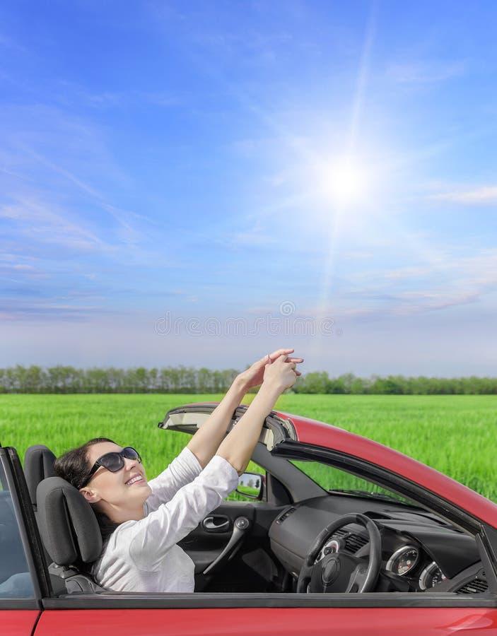 休息在一辆汽车的轮子的愉快的妇女在乡下公路的在s 免版税库存照片