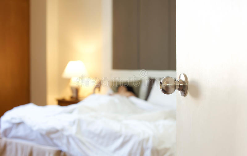 休息在与门的床上的睡觉的妇女打开 库存照片