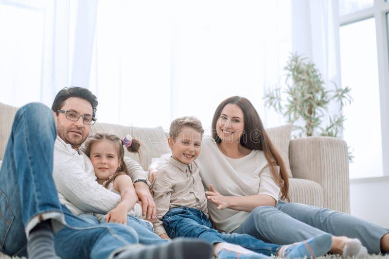 休息在他们舒适的客厅的愉快的家庭 图库摄影