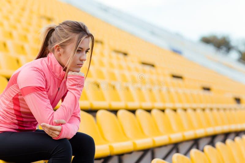 休息在体育场的体育穿戴的妇女 库存照片