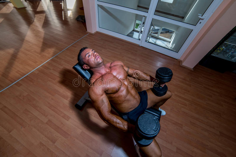休息在做的男性爱好健美者重量级的锻炼以后 库存照片