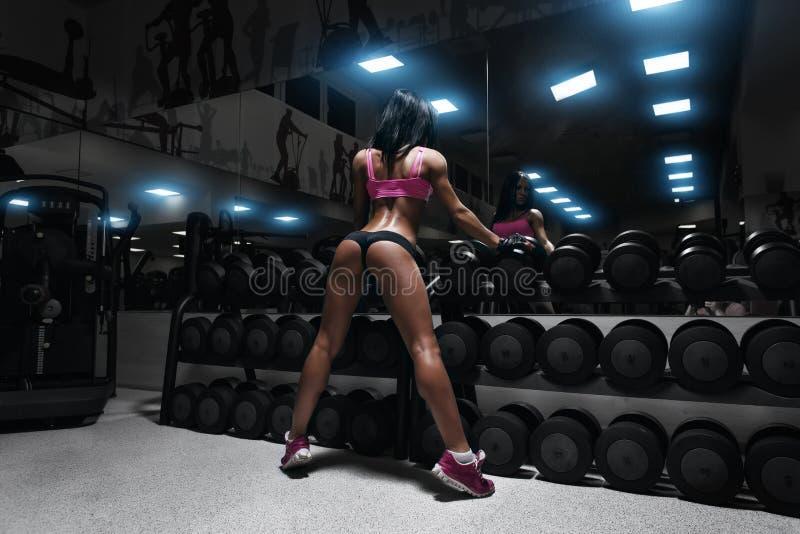 休息在健身房的后面观点的性感的年轻深色的妇女 免版税库存照片