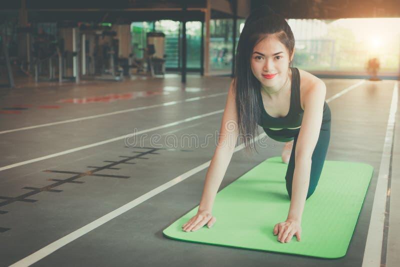 休息在健身房的美丽的亭亭玉立的少妇 肌肉女孩佩带的运动服,坐锻炼席子 免版税图库摄影