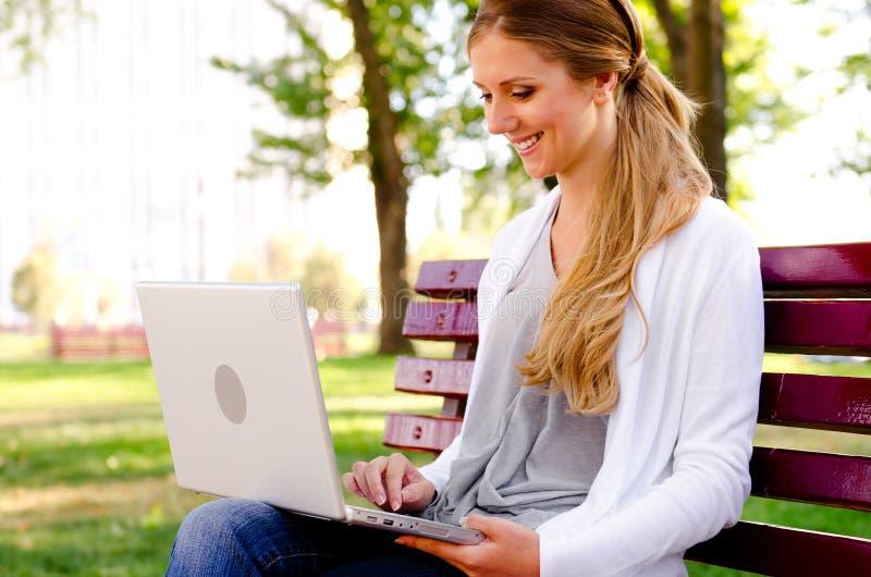 休息在公园和使用膝上型计算机的妇女 免版税库存照片