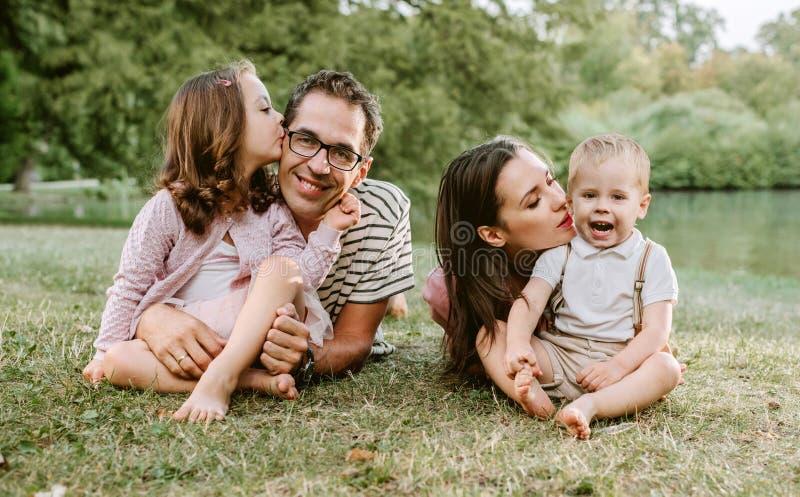 休息在公园的快乐的家庭画象 免版税库存图片