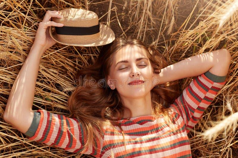 休息在农田的女孩接近的画象,在手中摆在与闭合的眼睛,holdiong她的草帽,穿镶边衬衣, 免版税库存照片