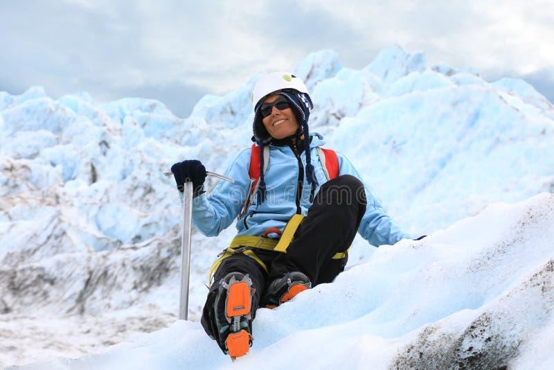 休息在冰川顶部的妇女登山人 免版税库存照片