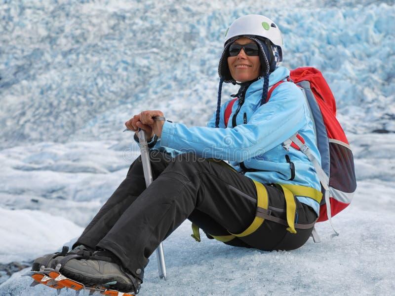 休息在冰川顶部的少妇登山人 免版税图库摄影