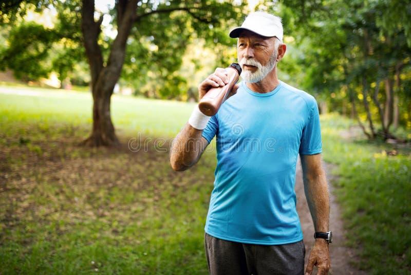 运动成熟人画象在奔跑以后的 休息在凹凸部以后的英俊的老人在公园 图库摄影