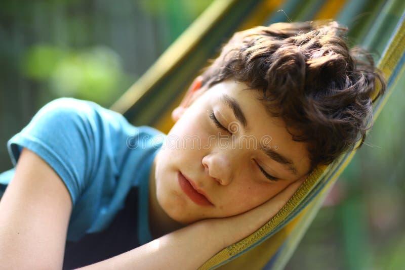 休息在吊床的少年男孩 免版税库存照片