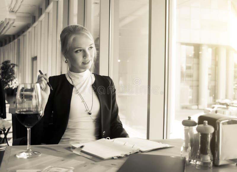 休息在咖啡馆的年轻女人画象 免版税库存图片