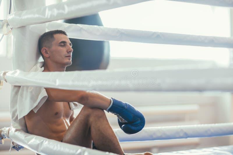 休息在圆环的角落的疲乏的运动员 免版税库存照片