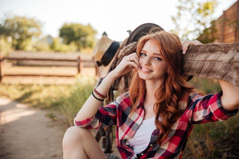 休息在大农场篱芭的快乐的逗人喜爱的红头发人女牛仔 库存照片