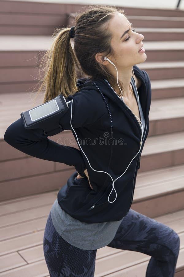 休息在奔跑以后的年轻女人的画象 免版税库存照片