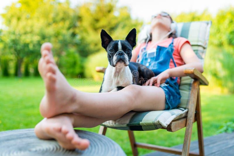休息在庭院里的狗和十几岁的女孩 库存照片