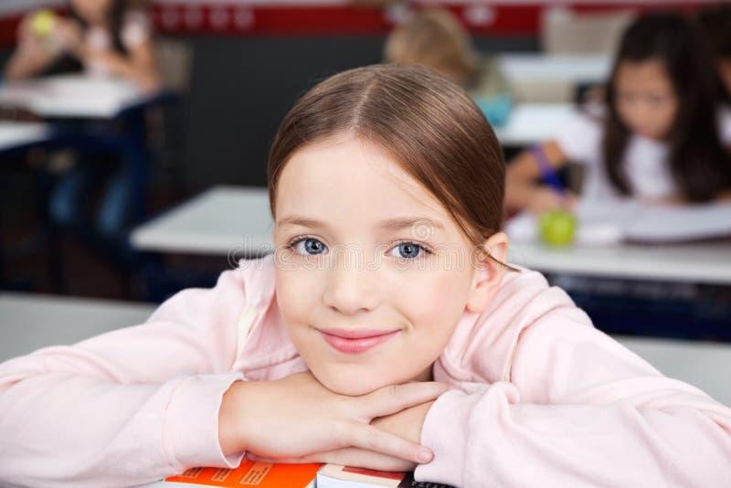 休息在手上的女小学生奇恩角在教室 免版税库存图片