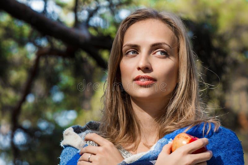 休息在春天或秋天森林里的美丽的白肤金发的女孩用红色苹果在她的手上 确信的白种人少妇 库存照片