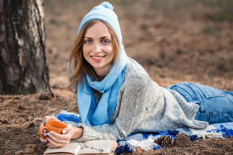 休息在春天或秋天森林里的美丽的白肤金发的女孩读了书,并且,说谎与茶和书 确信的白种人 免版税库存图片
