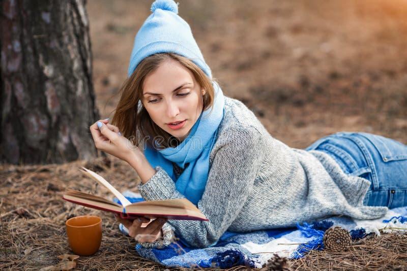 休息在春天或秋天森林里的美丽的白肤金发的女孩读了书,并且,说谎与茶和书 确信的白种人 库存图片
