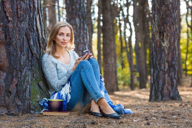 休息在森林里的美丽的白肤金发的女孩由手机讲话和,坐与茶和书 确信的白种人 免版税库存图片