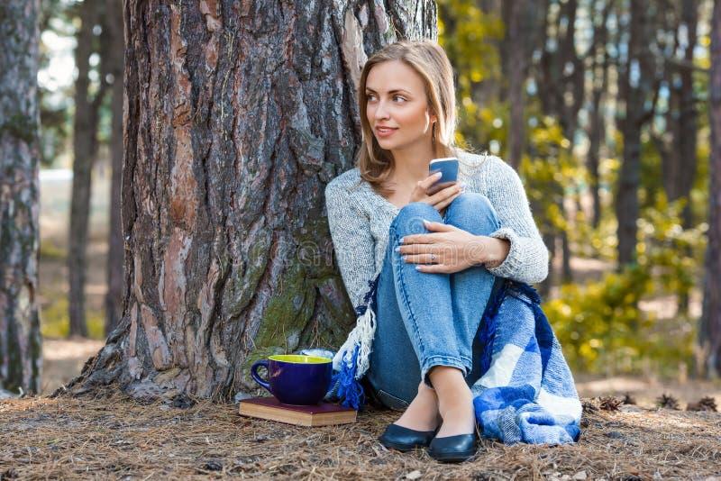 休息在森林里的美丽的白肤金发的女孩由手机讲话和,坐与茶和书 确信的白种人 免版税库存照片