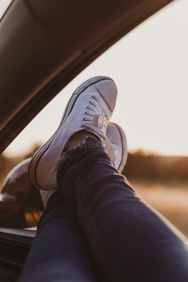 休息在汽车和敬佩看法的现代行家女孩 妇女司机观看的日落在车门上把脚放 脚窗口外 库存照片