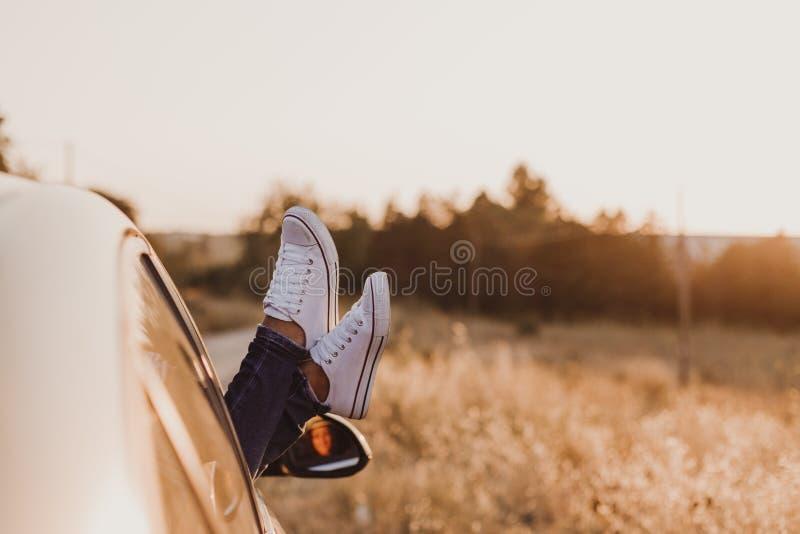 休息在汽车和敬佩看法的现代行家女孩 妇女司机观看的日落在车门上把脚放 脚窗口外 免版税库存照片