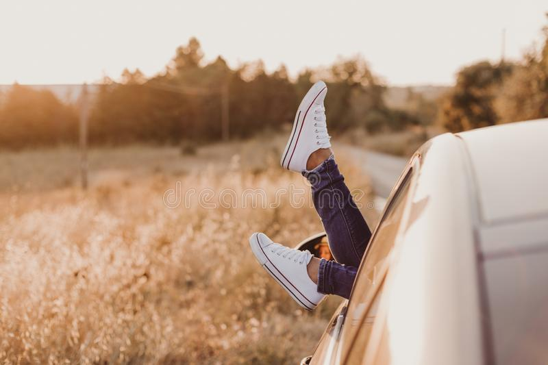休息在汽车和敬佩看法的现代行家女孩 妇女司机观看的日落在车门上把脚放 脚窗口外 免版税图库摄影