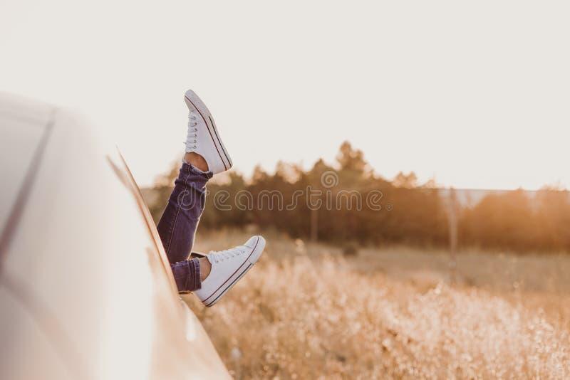 休息在汽车和敬佩看法的现代行家女孩 妇女司机观看的日落在车门上把脚放 脚窗口外 图库摄影
