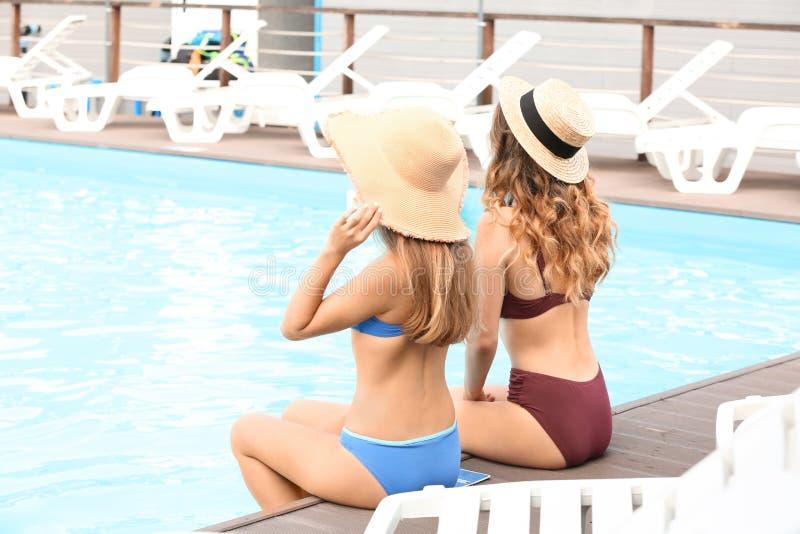 休息在游泳场附近的比基尼泳装的美丽的年轻女人 库存图片