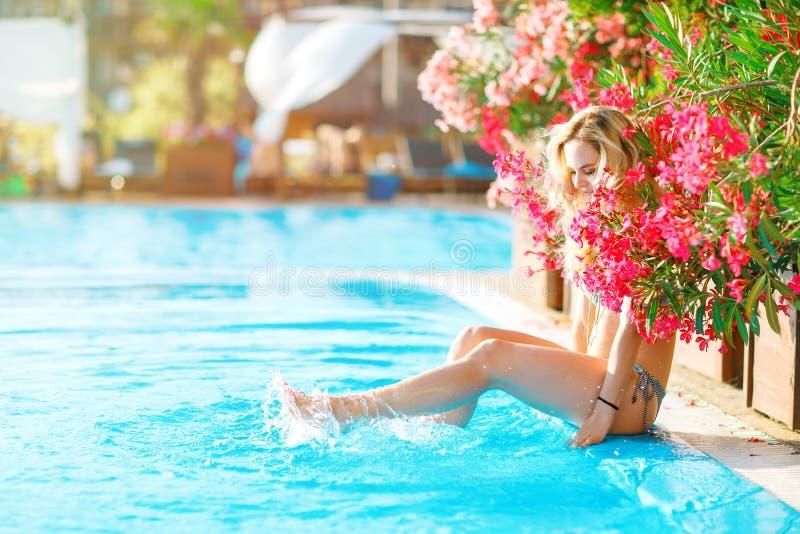 休息在游泳池的年轻美丽的白肤金发的妇女 免版税图库摄影