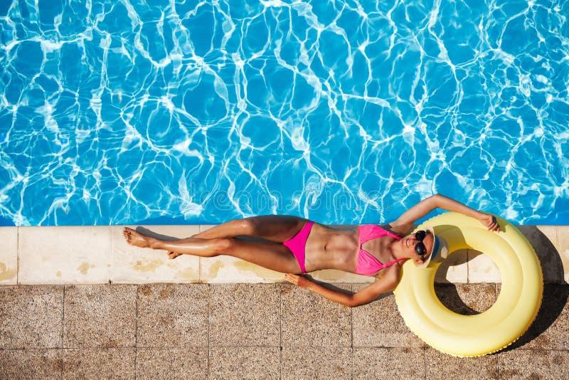 休息在游泳池附近的愉快的少妇 免版税库存图片