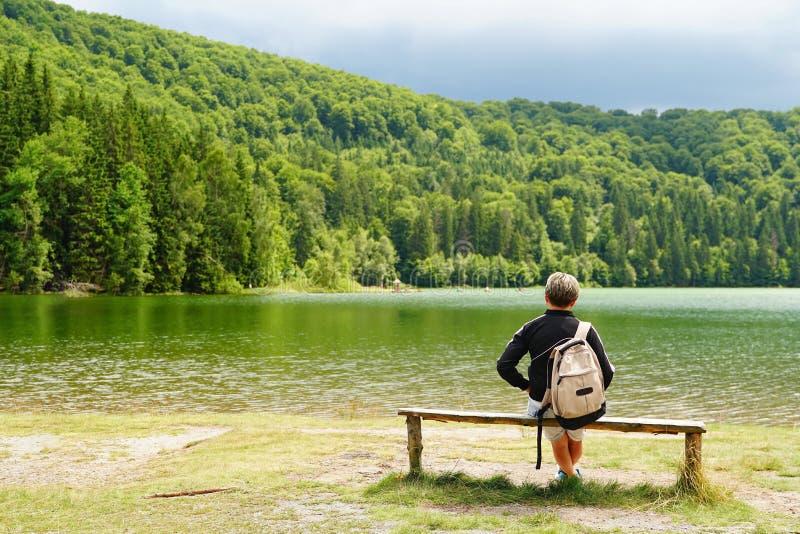 休息在湖附近的妇女 免版税库存图片